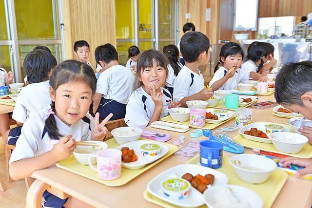 恵光幼稚園の園児が楽しそうに給食を食べている様子