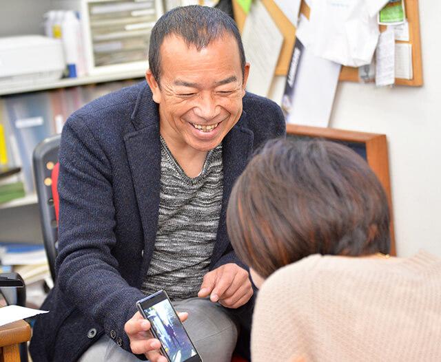 息子の写真を見せてくれている齋藤社長さん