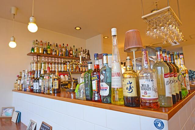 カウンターや壁の棚にたくさん並んでいるお酒