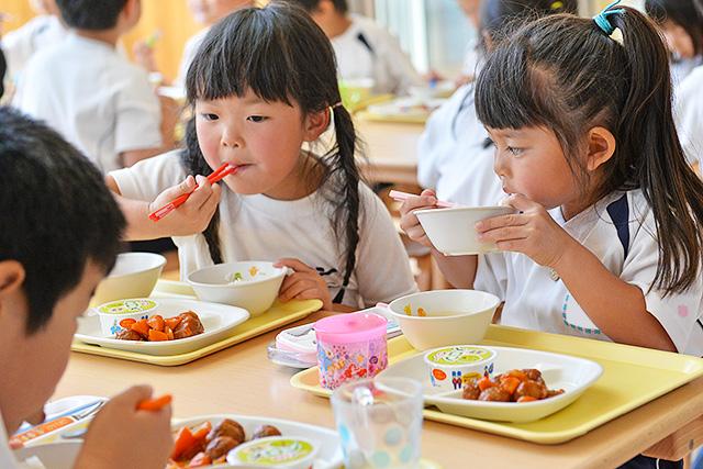 恵光幼稚園の園児たちがおいしそうに給食を食べている様子