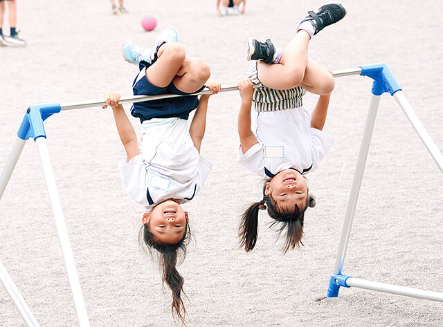 恵光幼稚園の園児が鉄棒で遊んでいる様子
