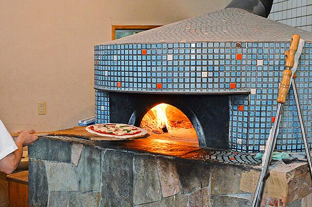 青のモザイク風タイルのピザ窯でピッツァを焼く様子