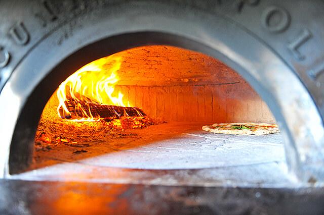 ピザ窯でピッツァを焼いている様子