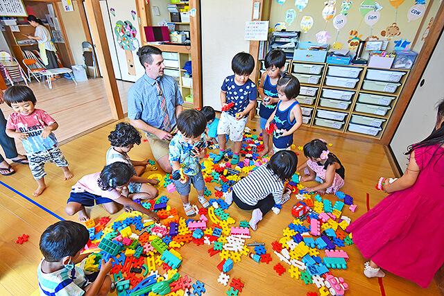 アイエルワイの園児と先生がカラフルなおもちゃで遊んでいる様子