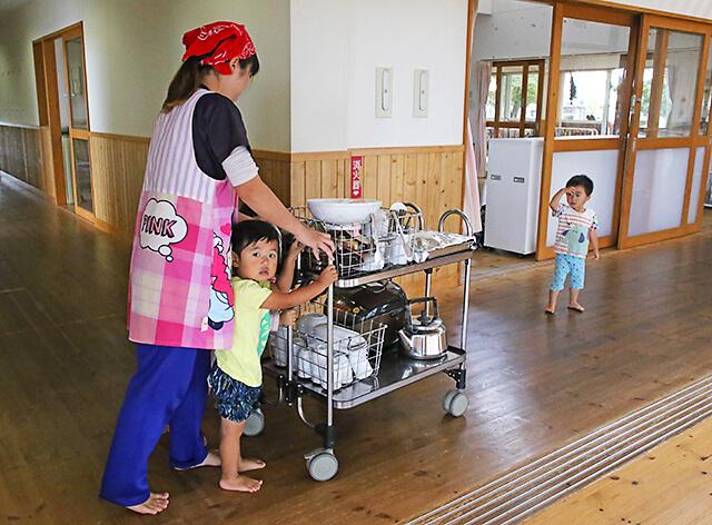 たんぽぽ保育園 先生と一緒に給食を運ぶ園児