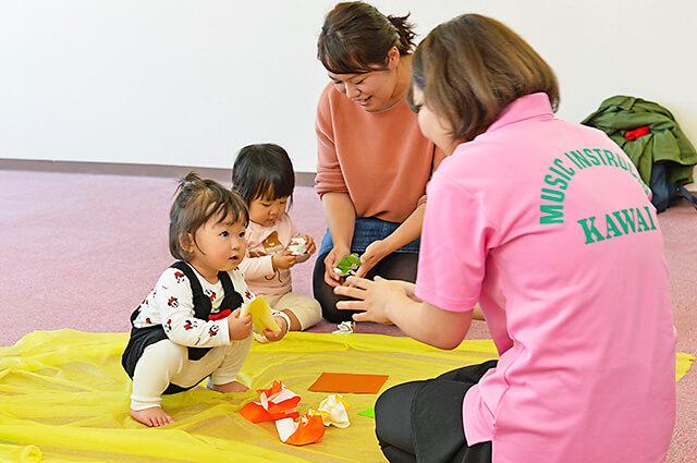 カワイ音楽教室 宇都宮東センターの親子リトミック 折り紙を先生やママと一緒にくしゃくしゃに丸めている様子