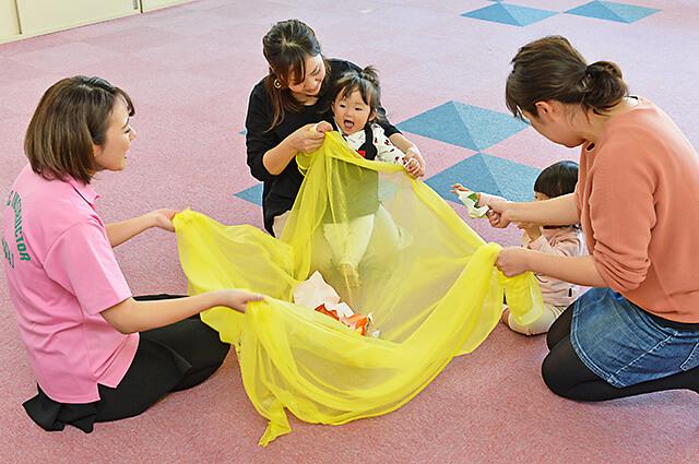 カワイ音楽教室 宇都宮東センターの親子リトミック 布に丸めた折り紙をのせてゆらゆら