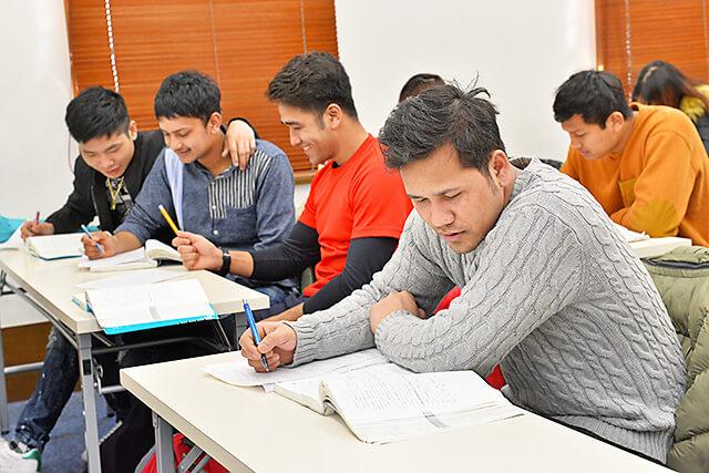 アティスインターナショナル日本語学校 出題されたテーマに沿って真剣に文章を書いている生徒さんたち