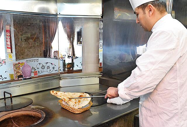 タージマハル 窯から焼きあがったナンを取り出している様子