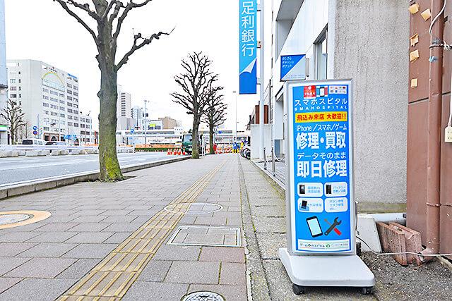 スマホスピタル 宇都宮店 入口に置かれた青いスタンド看板