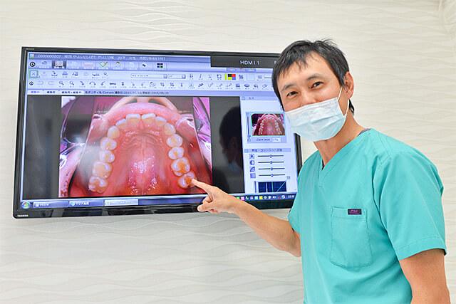 しのざき歯科医院 院長先生がモニターを使って説明している様子